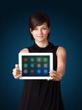 Mulher que guardara a tabuleta moderna com ícones coloridos Foto de Stock