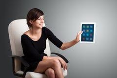 Mulher que guardara a tabuleta moderna com ícones coloridos Imagens de Stock Royalty Free