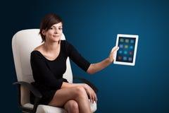 Mulher que guardara a tabuleta moderna com ícones coloridos Fotografia de Stock Royalty Free