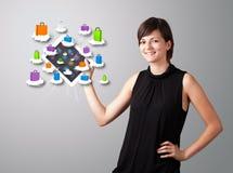 Mulher que guardara a tabuleta moderna com os sacos de compras coloridos na nuvem Fotografia de Stock Royalty Free