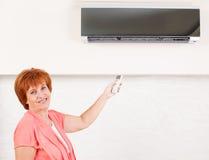 Mulher que guardara um condicionador de ar de controle remoto imagens de stock royalty free