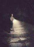 Mulher que guardara uma Bíblia de incandescência na floresta fotografia de stock royalty free