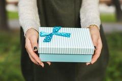 Mulher que guardara uma caixa de presente Fotografia de Stock Royalty Free