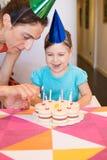 Mulher que ilumina velas no sorriso do bolo e da criança de aniversário imagens de stock