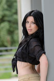 Mulher que inclina-se contra a parede enquanto vestindo uma camisa preta amarrada em um nó Foto de Stock Royalty Free