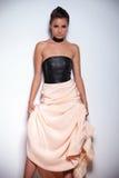 Mulher que inclina-se contra uma parede e que sustenta seu vestido bonito imagens de stock royalty free