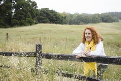 Mulher que inclina-se na cerca foto de stock royalty free