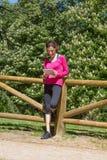 Mulher que inclina-se na tabuleta de observação da cerca de madeira Imagem de Stock Royalty Free