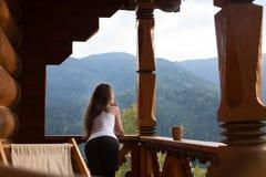 A mulher que inclina-se no corrimão de madeira e aprecia e relaxa a montanha bonita cênico Fêmea nova no terraço que inclina-se s Fotos de Stock