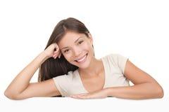 Mulher que inclina-se no sinal branco em branco do quadro de avisos Imagem de Stock Royalty Free