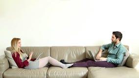 Mulher que inclina-se no sofá que explica algo ao homem de assento video estoque