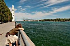 Mulher que inclina-se no trilho que negligencia o St Lawrence Imagem de Stock