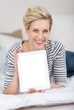 Mulher que indica a tabuleta de Digitas ao encontrar-se na cama Fotos de Stock Royalty Free