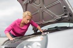 Mulher que inspeciona o motor de automóveis quebrado Fotografia de Stock