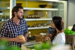 Mulher que interage com o vendedor ao comprar vegetais foto de stock