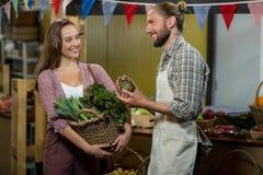 Mulher que interage com o vendedor ao guardar a cesta de legumes verdes fotos de stock royalty free