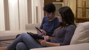 Mulher que introduz dados no PC da tabuleta do telefone esperto do noivo usando a tecnologia em casa filme
