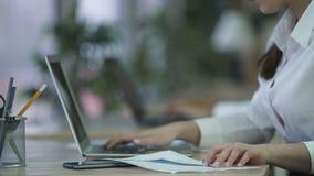 Mulher que introduz dados no portátil dos originais de papel, preparando o relatório no escritório vídeos de arquivo