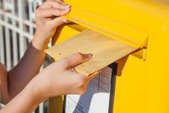 Mulher que introduz o envelope na caixa postal Imagem de Stock