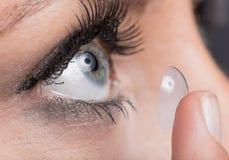 Mulher que introduz uma lente de contato foto de stock