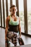Mulher que investe contra com pesos no gym imagens de stock royalty free