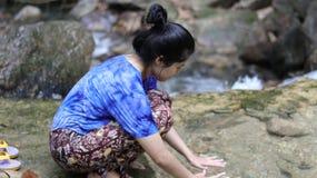 Mulher que joga as mãos na água em uma cachoeira Fotografia de Stock