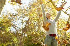 Mulher que joga Autumn Leaves In The Air Imagens de Stock