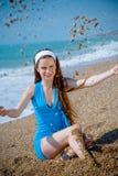 Mulher que joga com a areia na praia Fotografia de Stock