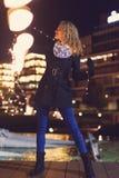 Mulher que joga com luzes feericamente do diodo emissor de luz da festão do Natal fora foto de stock royalty free