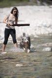 Mulher que joga com seu cão farpado da collie na água Imagens de Stock Royalty Free