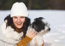 Mulher que joga com seu cão na neve Imagem de Stock