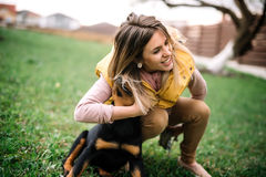 Mulher que joga e que abraça seu cachorrinho em um fim da tarde Fotos de Stock