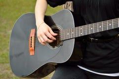 Mulher que joga a guitarra preta Fotos de Stock