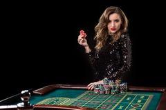 Mulher que joga no casino A mulher estaca pilhas das microplaquetas que jogam o rou imagem de stock