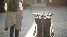 Mulher que joga o escaninho de reciclagem próximo de papel vazio do copo de café, fundo da cidade Reciclando, conceito amigável d video estoque