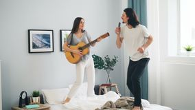 Mulher que joga o indivíduo da guitarra que canta no controlo a distância e que dança na cama em casa video estoque