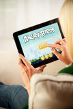 Mulher que joga o jogo de vídeo irritado dos pássaros no iPad 1 de Apple Fotografia de Stock