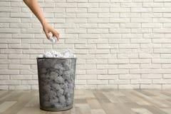 Mulher que joga o papel amarrotado no escaninho do metal no assoalho contra a parede de tijolo, close up fotografia de stock