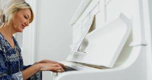Mulher que joga o piano em casa 4k vídeos de arquivo