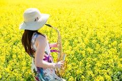 Mulher que joga o saxofone no campo da colza Imagem de Stock