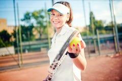 Mulher que joga o tênis, guardando a raquete e a bola T-shirt branco vestindo e tampão da menina moreno atrativa no campo de têni Imagem de Stock