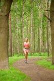 Mulher que joga os esportes, correndo no parque fotografia de stock royalty free