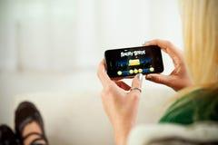 Mulher que joga pássaros irritados no iPhone 4 de Apple Imagem de Stock Royalty Free