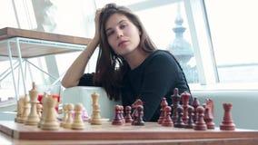 Mulher que joga a posição interna e pensando da xadrez, movimento de vencimento do achado, estratégia HD filme