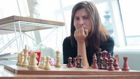 Mulher que joga a posição interna e pensando da xadrez, movimento de vencimento do achado, perfuração da estratégia filme
