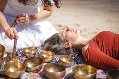 A mulher que joga um canto rola igualmente sabido como bacias do canto do tibetano, bacias Himalaias Fazendo a massagem sadia Imagem de Stock Royalty Free