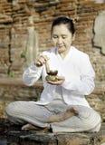 Mulher que joga uma bacia tibetana, usada tradicional para ajudar ao meditati imagem de stock