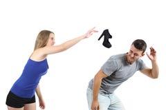 Mulher que joga uma sapata do salto para um homem Imagens de Stock Royalty Free