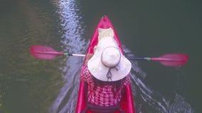 Mulher que kayaking na câmera pov da ação da opinião de ângulo superior da lagoa da menina que rema no barco do caiaque vídeos de arquivo