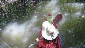 Mulher que kayaking na opinião traseira traseira do pov da câmera tropical da ação do rio a menina que rema no barco do caiaque filme